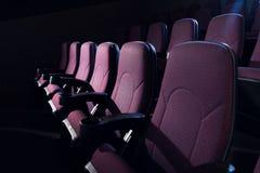 κόκκινα καθίσματα στο κενό σκοτάδι Στοκ Εικόνες