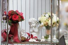 Κόκκινα και άσπρα γαμήλιες ανθοδέσμες και αντικείμενα διακοσμήσεων Στοκ Φωτογραφία