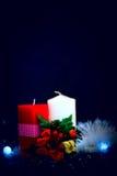 Κόκκινα και άσπρα κεριά με τη γιρλάντα στο μαύρο υπόβαθρο Στοκ Φωτογραφίες