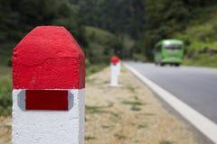 Κόκκινα και άσπρα χρωματισμένα κύρια σημεία στη σειρά σε μια εθνική οδό Στοκ Φωτογραφίες