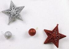 Κόκκινα και ασημένια αστέρια Χριστουγέννων με το ακτινοβολώντας άσπρο υπόβαθρο στοκ εικόνα