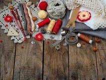 Κόκκινα και γκρίζα εξαρτήματα για τη ραπτική στο ξύλινο υπόβαθρο Πλέξιμο, κεντητική, ράψιμο η τρισδιάστατη επιχείρηση απομόνωσε τ Στοκ Εικόνα