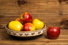 Κόκκινα και κίτρινα μήλα στο ξύλινο πιάτο στο αγροτικό υπόβαθρο Στοκ Εικόνα