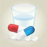 Κόκκινα και μπλε pillules με τα άσπρα χάπια και το ποτήρι του νερού στο lig Στοκ Φωτογραφία