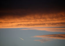 Κόκκινα και πορτοκαλιά σύννεφα στο ηλιοβασίλεμα με το ίχνος ατμού αεροσκαφών αεριωθούμενων αεροπλάνων Στοκ φωτογραφία με δικαίωμα ελεύθερης χρήσης