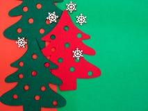 κόκκινα και πράσινα αισθητά δέντρα πεύκων με ξύλινα snowflakes Στοκ Εικόνες