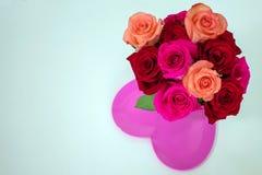Κόκκινα και ρόδινα τριαντάφυλλα στο φωτεινό ρόδινο διαμορφωμένο καρδιά πιάτο στοκ εικόνες με δικαίωμα ελεύθερης χρήσης