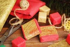 Κόκκινα και χρυσά κιβώτια δώρων και έγγραφο τεχνών για το ξύλο Στοκ Φωτογραφίες