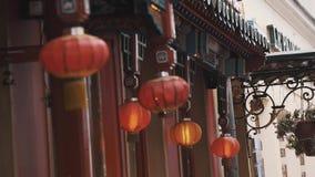 Κόκκινα και χρυσά κινεζικά φανάρια ύφους που κρεμούν υπαίθρια στο μέρος εστιατορίων απόθεμα βίντεο