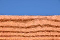 Κόκκινα καφετιά κεραμικά κεραμίδια στεγών πέρα από το μπλε ουρανό στοκ εικόνες