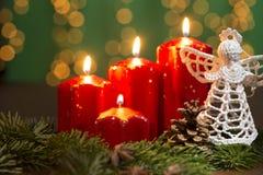 Κόκκινα κεριά εμφάνισης στο παλαιό ξύλινο υπόβαθρο με την ελαφριά κουρτίνα Χριστουγέννων Στοκ Φωτογραφία