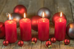 Κόκκινα κεριά εμφάνισης Χριστουγέννων με τις διακοσμήσεις σφαιρών στοκ φωτογραφία με δικαίωμα ελεύθερης χρήσης