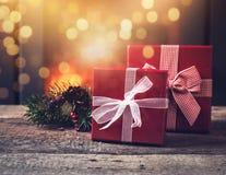 κόκκινα κιβώτια των δώρων Χριστουγέννων στον ξύλινο πίνακα - καίγοντας εστία Στοκ εικόνες με δικαίωμα ελεύθερης χρήσης