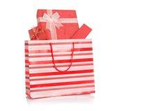Κόκκινα κιβώτια δώρων στην κόκκινη τσάντα αγορών Στοκ Φωτογραφίες