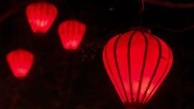 Κόκκινα κινεζικά φανάρια LIT κινηματογραφήσεων σε πρώτο πλάνο στο σκοτεινό νυχτερινό ουρανό φιλμ μικρού μήκους
