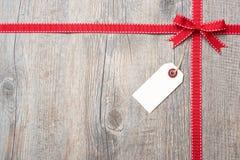 Κόκκινα κορδέλλα και τόξο με την ετικέτα προσφωνήσεων Στοκ φωτογραφία με δικαίωμα ελεύθερης χρήσης