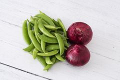 Κόκκινα κρεμμύδια και αιφνιδιαστικά μπιζέλια ζάχαρης ένα από πέντε σας ημερησίως στην υγιή κατανάλωση στοκ φωτογραφίες
