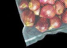 Κόκκινα κρεμμύδια στην τσάντα πλέγματος και μερικά στο πάτωμα στο μαύρο backg Στοκ Εικόνες
