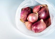 Κόκκινα κρεμμύδια στην τσάντα πλέγματος στο άσπρο υπόβαθρο Στοκ Φωτογραφία