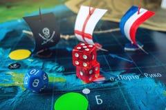 Κόκκινα κόκκαλα παιχνιδιού στον παγκόσμιο χάρτη των χειροποίητων επιτραπέζιων παιχνιδιών τομέων με ένα σκάφος πειρατών Στοκ Φωτογραφίες