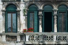 Κόκκινα λουλούδια σε ένα εκλεκτής ποιότητας μπαλκόνι στη Βενετία Στοκ Εικόνες