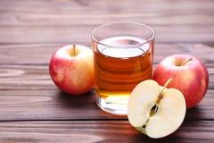 Κόκκινα μήλα με το χυμό σε ένα καφετί υπόβαθρο στοκ φωτογραφίες