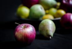 Κόκκινα μήλα, πράσινα αχλάδια και κίτρινα κυδώνια στο σκοτεινό υπόβαθρο Στοκ φωτογραφία με δικαίωμα ελεύθερης χρήσης