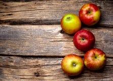 Κόκκινα μήλα στο ξύλινο υπόβαθρο Στοκ Φωτογραφία