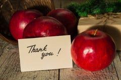 Κόκκινα μήλα με ένα δώρο και μια κάρτα Στοκ Εικόνα