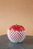 Κόκκινα μήλα με την προστατευτική συσκευασία στο πάτωμα πετρών Στοκ Εικόνα