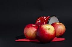 Κόκκινα μήλα με το φλυτζάνι στο μαύρο υπόβαθρο Στοκ φωτογραφία με δικαίωμα ελεύθερης χρήσης
