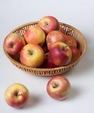 Κόκκινα μήλα σε ένα καλάθι στο άσπρο υπόβαθρο Στοκ Φωτογραφίες