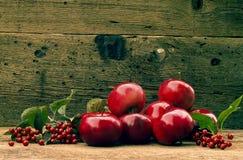 Κόκκινα μήλα σε ένα ξύλινο υπόβαθρο Στοκ Εικόνες