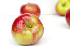 Κόκκινα μήλα στην άσπρη επιφάνεια με το άσπρο υπόβαθρο Στοκ Εικόνα