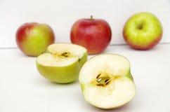 Κόκκινα μήλα στην άσπρη επιφάνεια με το άσπρο υπόβαθρο Στοκ Φωτογραφίες
