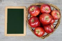 Κόκκινα μήλα στο καλάθι με μια μικρή πλάκα Στοκ εικόνα με δικαίωμα ελεύθερης χρήσης