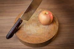 Κόκκινα μήλο και μαχαίρι στον ξύλινο τέμνοντα πίνακα Στοκ εικόνες με δικαίωμα ελεύθερης χρήσης