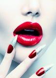 Κόκκινα μακριά καρφιά και κόκκινα στιλπνά χείλια Στοκ εικόνα με δικαίωμα ελεύθερης χρήσης