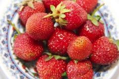 κόκκινα μούρα μιας φράουλας σε ένα πιάτο στο υπόβαθρο στοκ φωτογραφία