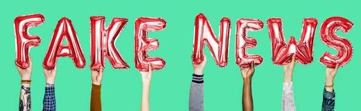 Κόκκινα μπαλόνια ηλίου αλφάβητου που διαμορφώνουν τις πλαστές ειδήσεις κειμένων στοκ εικόνες με δικαίωμα ελεύθερης χρήσης