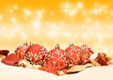 Κόκκινα μπιχλιμπίδια Χριστουγέννων στη χρυσή ανασκόπηση Στοκ Εικόνα