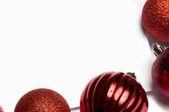 Κόκκινα μπιχλιμπίδια Χριστουγέννων στην άσπρη σελίδα Στοκ Εικόνα