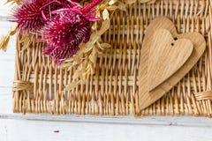 Κόκκινα λουλούδια και ξύλινες καρδιές Στοκ Φωτογραφία