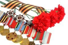Κόκκινα λουλούδια που δένονται με την κορδέλλα Αγίου George, μετάλλια, διαταγές Στοκ φωτογραφία με δικαίωμα ελεύθερης χρήσης