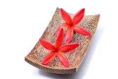 Κόκκινα λουλούδια Plumeria με το ξύλινο κύπελλο Στοκ Φωτογραφία