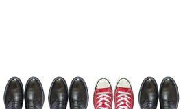Κόκκινα πάνινα παπούτσια και επιχειρησιακά παπούτσια ατόμων Στοκ Φωτογραφία