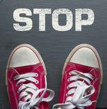 Κόκκινα πάνινα παπούτσια με το σημάδι στάσεων Στοκ Εικόνες
