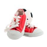 Κόκκινα πάνινα παπούτσια μωρών με μια σφαίρα που απομονώνεται στο λευκό Στοκ Εικόνα