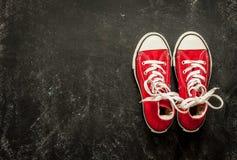 Κόκκινα πάνινα παπούτσια στο μαύρο πίνακα κιμωλίας - αθλητισμός Στοκ Φωτογραφίες