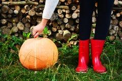 Κόκκινα παπούτσια βροχής κολοκύθας φθινοπώρου και ξύλινος με το υπόβαθρο leavs Στοκ Εικόνα